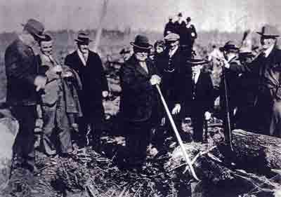 Photo: John W. Berry, MLS, planting tree No. 2 in the Inaugural Plantation, March 15, 1930. Others, left-right: Colonel Nelson Spencer, young Tom Berry, MLA Mike Manson, Peter Z. Caverhill (Chief Engineer), and Ed Walmsley (Land Agent), resting foot on log.