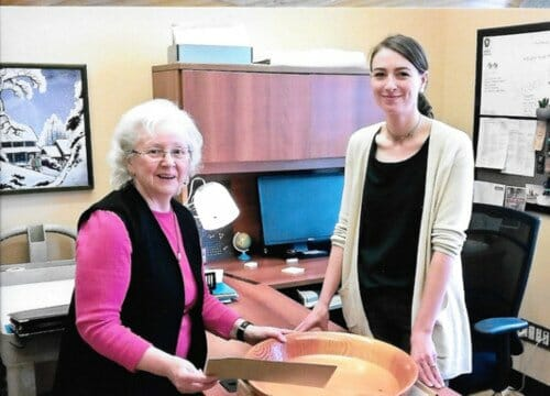 Ellen Edwards (daughter of John Tompson) and Kristin Hardie, archivist, examine the bowl